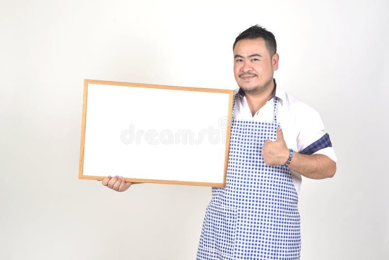 Торговый азиатский человек в белой и голубой рисберме к держать пустое белое обширное для положил некоторый текст или формулирова стоковая фотография