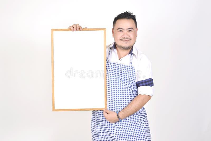 Торговый азиатский человек в белой и голубой рисберме к держать пустое белое обширное для положил некоторый текст или формулирова стоковое фото
