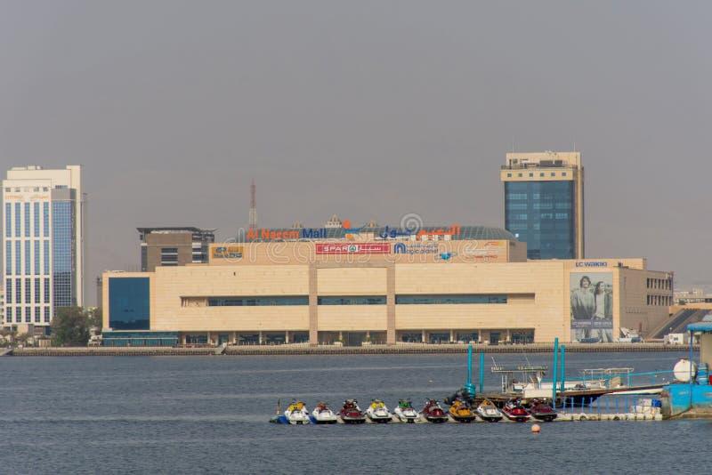 Торговый центр Naeem Al смотря вне от карниза около башен Julphar вдоль воды Хорошее туристское или проживающее назначение для хо стоковые фото