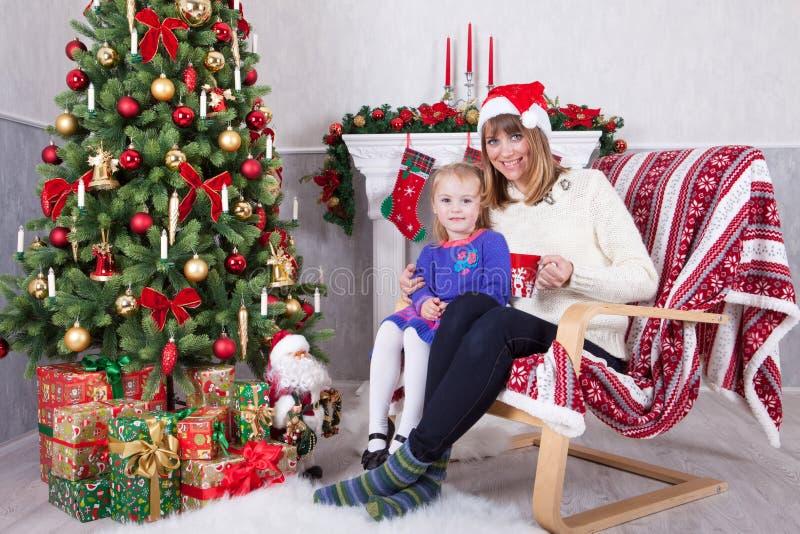 Торжество рождества или Нового Года Счастливая мать и дочь сидя в стуле около рождественской елки с подарками xmas Острословие ка стоковое фото rf