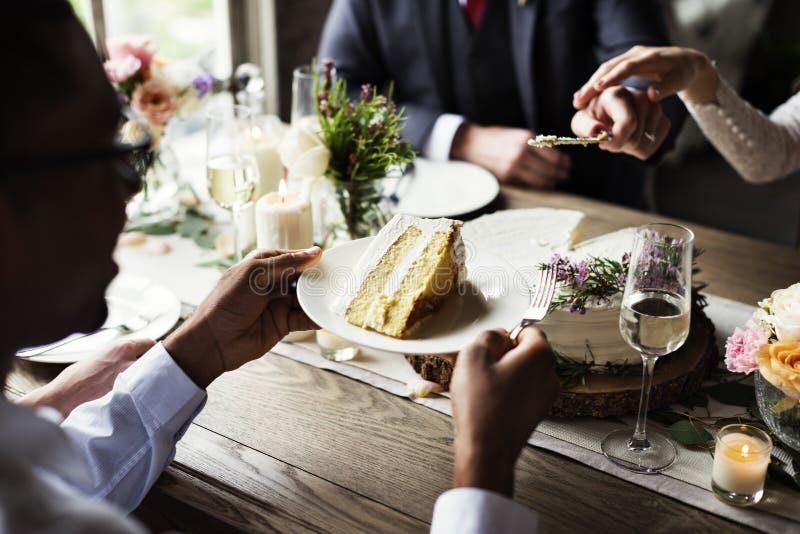 Торт вырезывания жениха и невеста на приеме по случаю бракосочетания стоковые фото