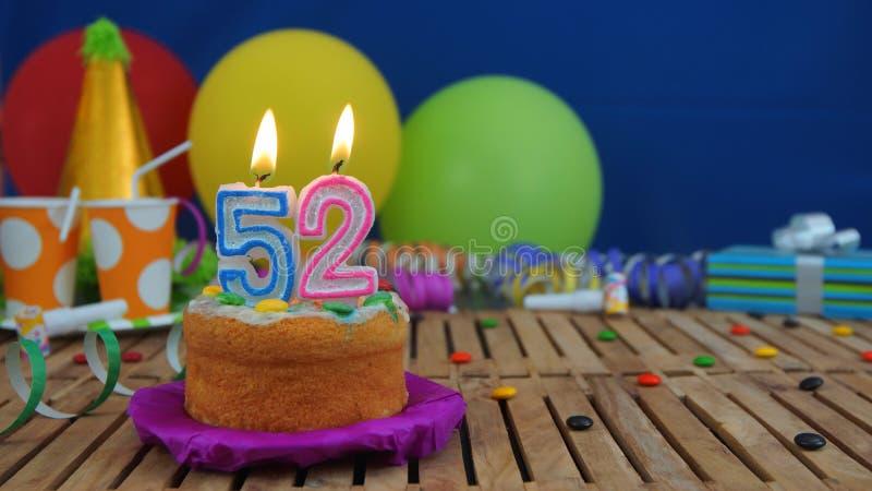 Торт дня рождения 52 со свечами на деревенском деревянном столе с предпосылкой красочных воздушных шаров, подарков, пластиковых ч стоковое фото