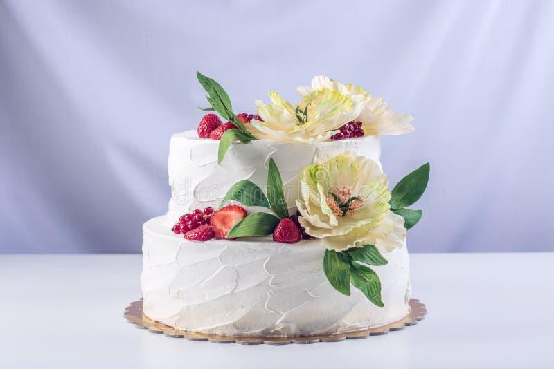 Торт домашней свадьбы 2-tiered украшенный с смородинами, клубниками и желтыми цветками Праздничный десерт ягоды стоковые изображения