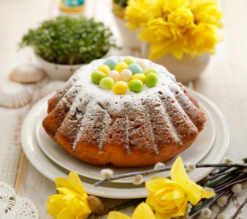 Торт дрожжей пасхи взбрызнутый с напудренным сахаром, украшенным с яйцами марципана стоковые изображения rf