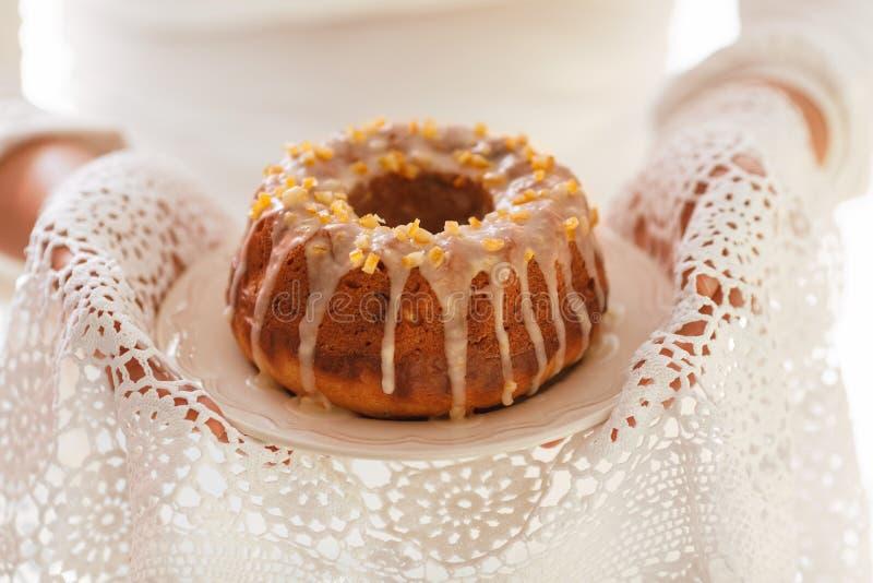 Торт дрожжей пасхи на белой плите держал женскими руками, при служении к таблице , стоковое изображение