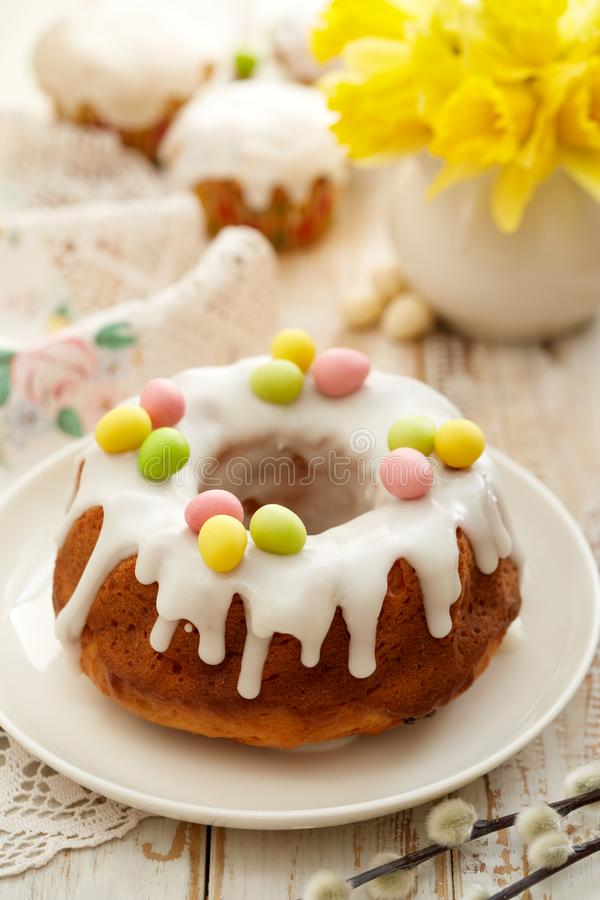 Торт дрожжей Babka пасхи покрытое с замороженностью и украшенное с яйцами марципана на белой плите на деревянном столе стоковое фото rf