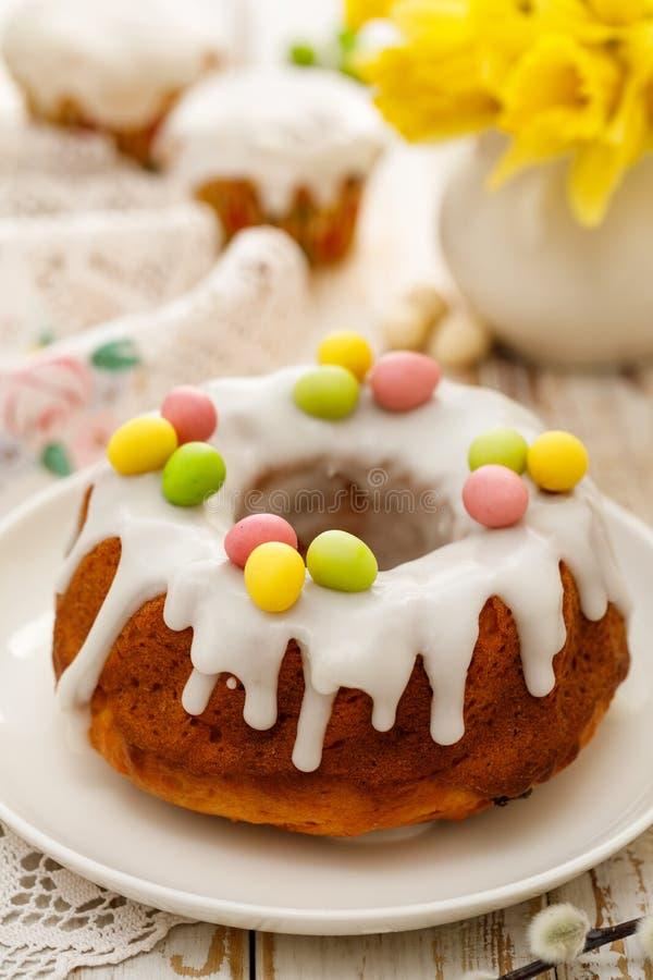 Торт дрожжей Babka пасхи покрытое с замороженностью и украшенное с яйцами марципана на белой плите на деревянном столе стоковые фото