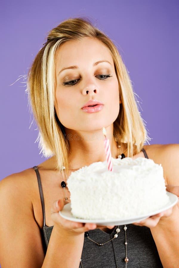 Торт: Женщина дуя вне свеча на именнином пироге стоковое изображение rf