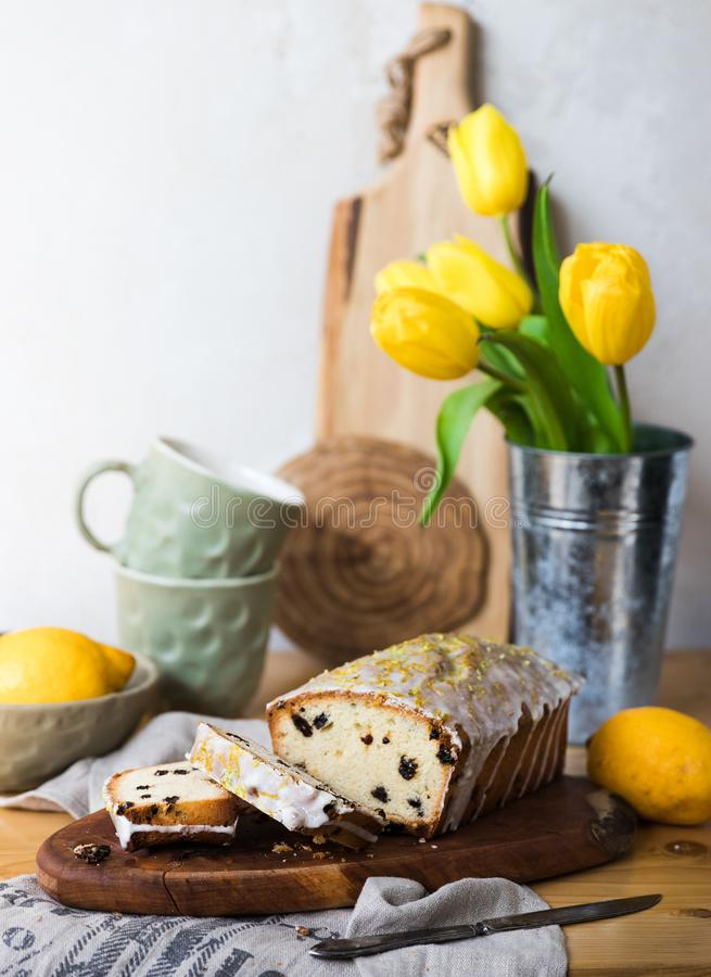 Торт изюминки на деревянной доске с лимоном и желтыми тюльпанами стоковые фотографии rf