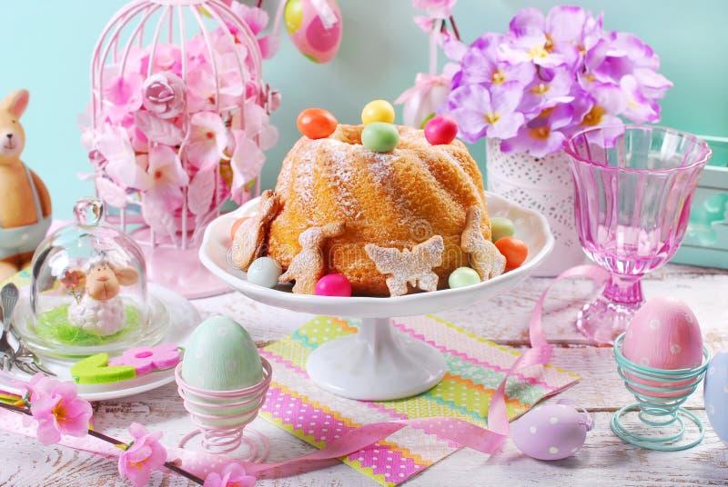 Торт кольца пасхи с яичками и печеньями конфеты на таблице весны стоковая фотография