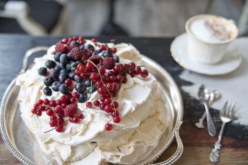 Торт меренги с ягодами на серебряном подносе и чашке кофе стоковые изображения rf