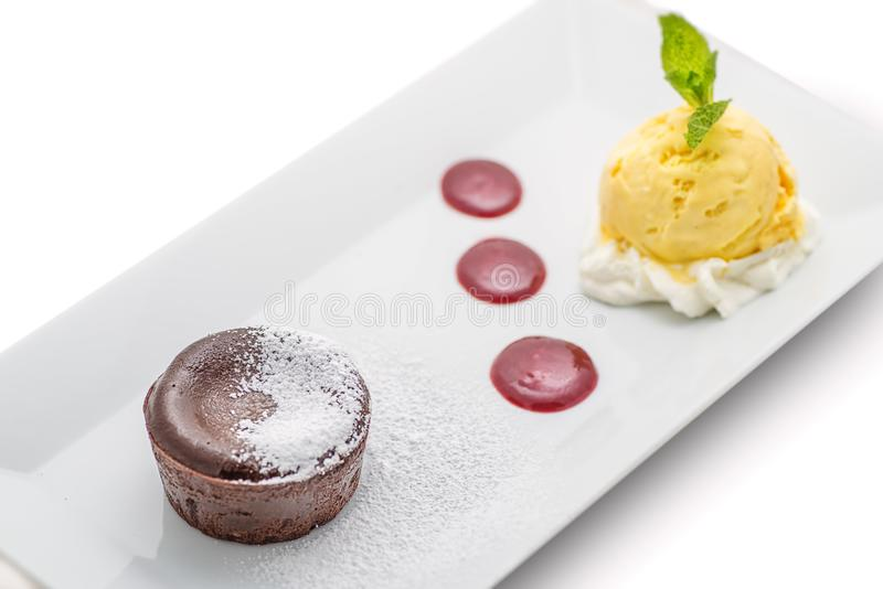 Торт очень вкусного шоколада горячий с соусом плодоовощ и мороженым ванили на белой плите, помадке шоколада стоковые изображения rf