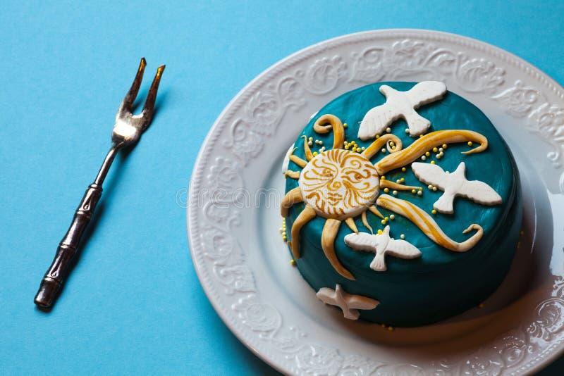 Торт пасхи голубой, желтое солнце и белые голуби в белой плите с вилкой background card congratulation invitation стоковые фото