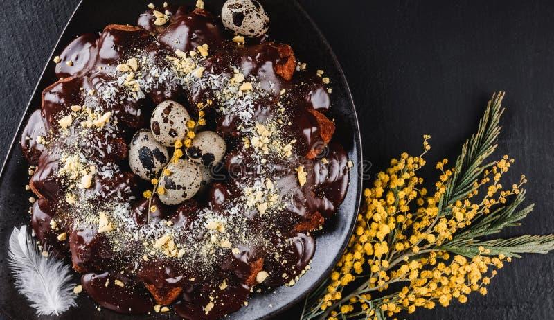 Торт пасхи с шоколадом, кокосом, цветками весны, яйцами триперсток на темной каменной предпосылке Счастливое торжество пасхи r стоковая фотография rf