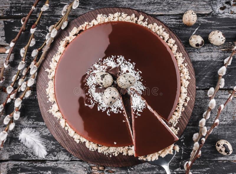 Торт пасхи с шоколадом поливы зеркала, кокосом, цветками весны, яйцами триперсток на деревенской предпосылке Счастливое торжество стоковые фотографии rf
