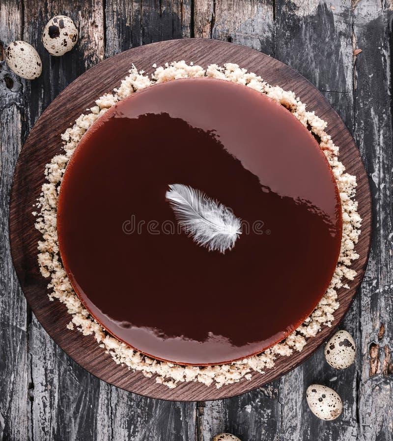 Торт пасхи с шоколадом поливы зеркала на деревенской предпосылке с цветками весны, яйцами триперсток Счастливое торжество пасхи стоковое изображение rf
