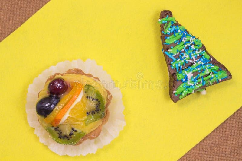 Торт пирожного и торт с плодоовощ на желтой предпосылке стоковое фото