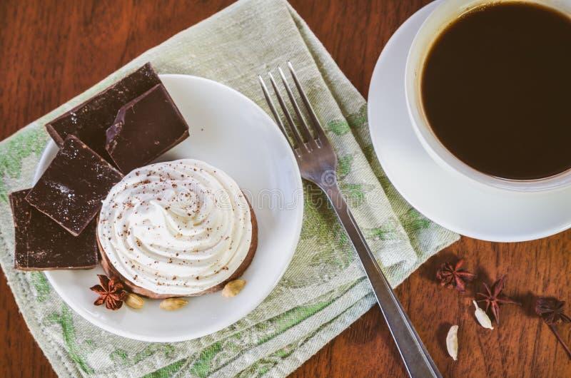 Торт со сливк яйца белой, части шоколада, анисовка, кардамон и вилка на зеленом serviette и чашка горячего кофе стоковое фото
