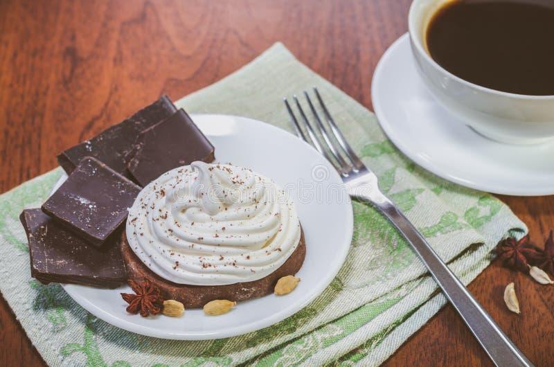 Торт со сливк яйца белой, части шоколада, анисовка, кардамон и вилка на зеленом serviette и чашка горячего кофе стоковые изображения