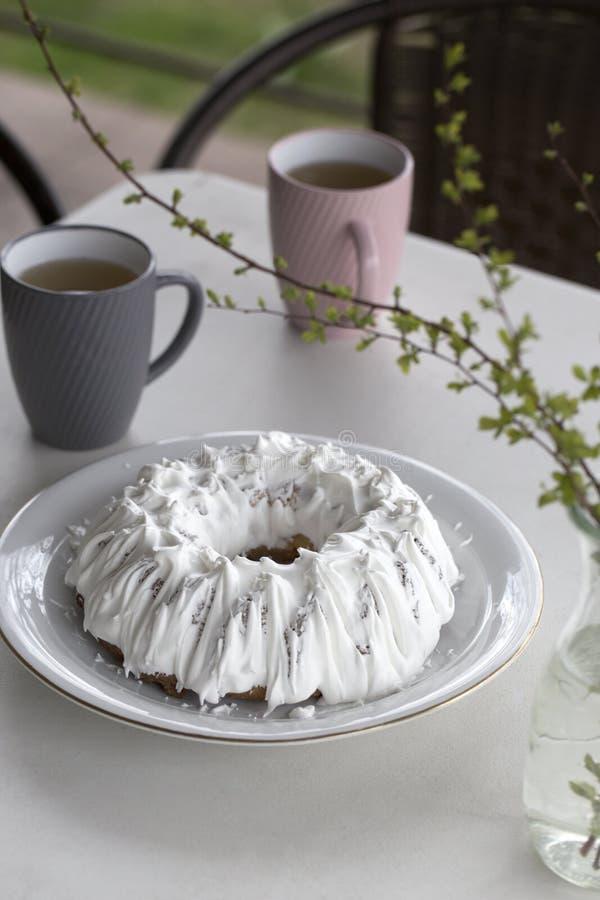 Домодельный торт с чаем Торт с замороженностью сахара Домодельный торт в форме кольца с чашками чаю или кофе на белой таблице стоковое фото