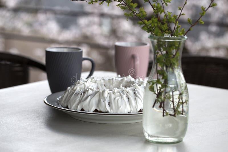 Домодельный торт с чаем Торт с замороженностью сахара Домодельный торт в форме кольца с чашками чаю или кофе на белой таблице стоковая фотография