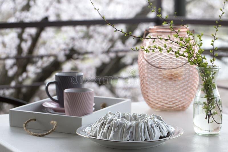 Домодельный торт с чаем Торт с замороженностью сахара Домодельный торт в форме кольца с чашками чаю или кофе на белой таблице стоковое изображение