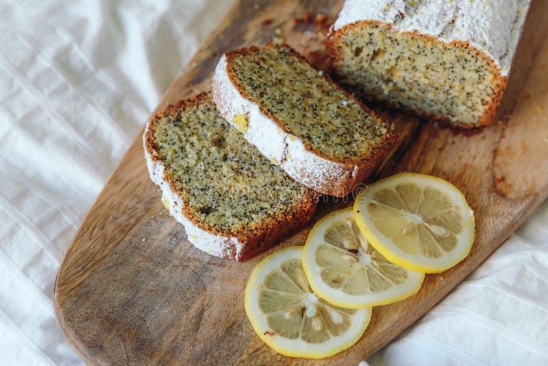 Торт с маковыми семененами и пылом лимона, взбрызнутыми с напудренным сахаром Пирожное с лимоном на деревянной доске стоковое изображение