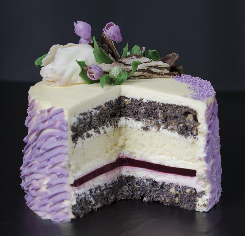 Торт творога с маковыми семененами и вареньем поленики Украшенный с белым шоколадом цветет на темной предпосылке Селективный фоку стоковое фото