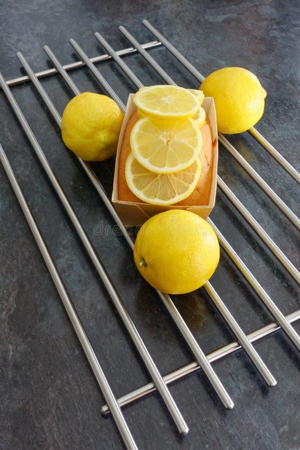 Торт хлебца лимона в форме коричневой бумаги украшенной с кусками лимона стоковое изображение
