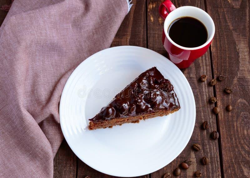 Торт шоколада и вишни Часть на белом конце-вверх плиты Чашка кофе стоковая фотография