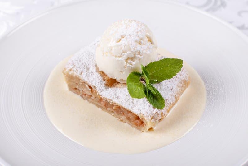 Торт штрудели яблока плодоовощ служил с мороженым, лист мяты и соусом ванили Классический австрийский десерт на белой плите стоковые фото