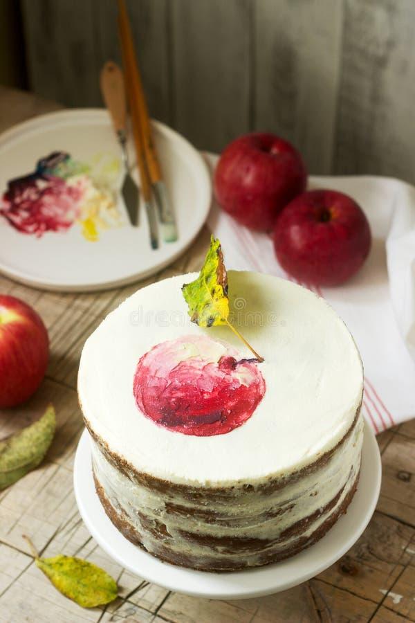 Торт Яблока со сливк творога, украшенной с покрашенным яблоком на предпосылке состава осени r стоковая фотография rf