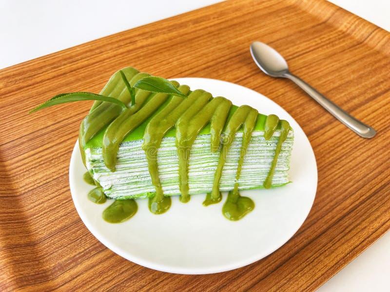 Торт crepe молока зеленого чая с свежими лист зеленого чая на белой керамических плите и ложке положенных на деревянный поднос стоковое фото
