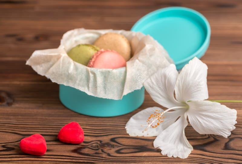 Торт Macarons в подарочной коробке, соединяет красные сердца и белый гибискус стоковое фото