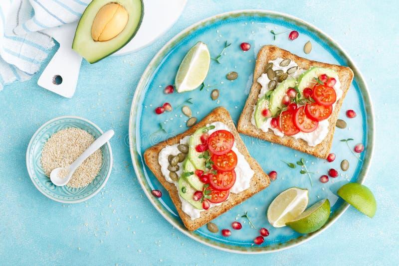 Тосты с сыром фета, томатами, авокадоом, гранатовым деревом, семенами тыквы и ростками льняного семени Завтрак диеты очень вкусны стоковое изображение rf