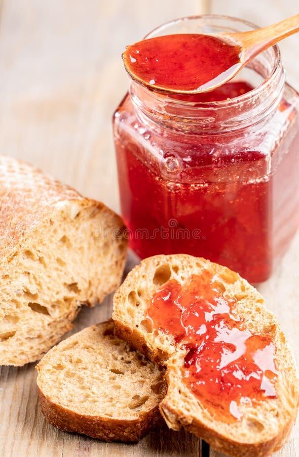 Тосты хлеба конца-вверх с вареньем клубники, деревянной ложкой и опарником с вареньем на деревянном столе стоковая фотография rf
