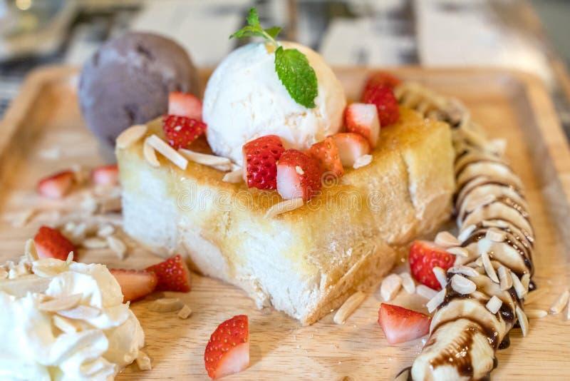 Тост меда клубники с мороженым на деревянном блюде плиты стоковое изображение
