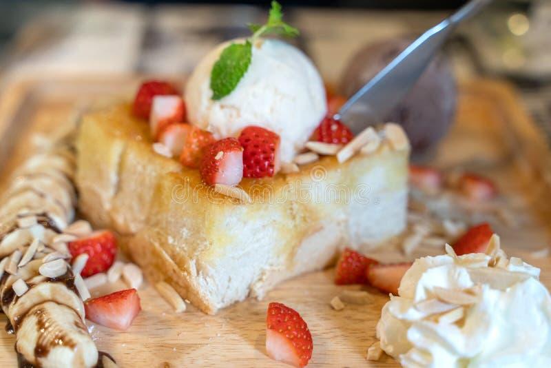 Тост меда клубники с мороженым на деревянном блюде плиты стоковая фотография