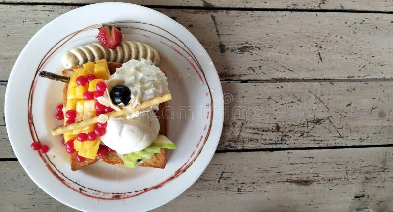 Тост меда плодов с мороженым и wipped сливк стоковое фото rf