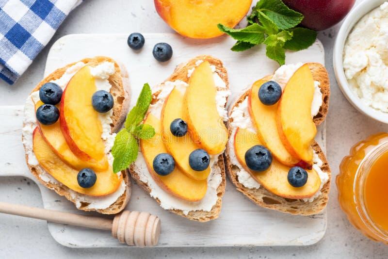 Тост с сыром, персиком, голубикой и медом рикотты стоковые фотографии rf