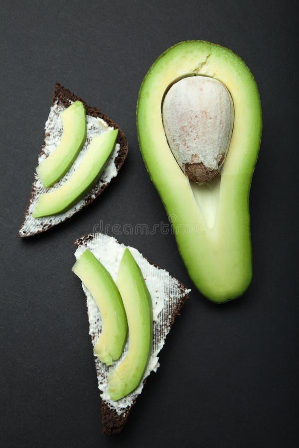 Тост черного хлеба и частей авокадоа на черной предпосылке, вертикально стоковая фотография rf