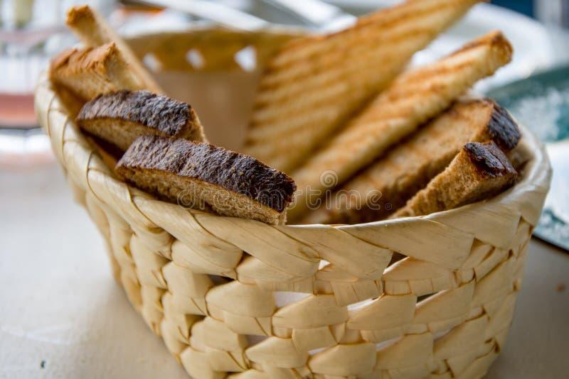 Тост-тост черный и белый хлеб лежит в деревянной корзине, обеденный сто стоковое фото rf