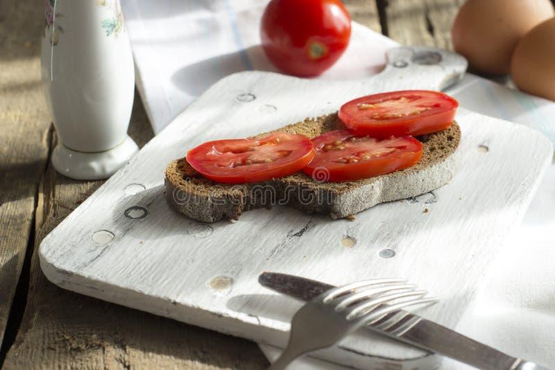 Тост Sourdough, с зажаренными томатами Здоровые, очень вкусные завтрак или завтрак-обед стоковые фото