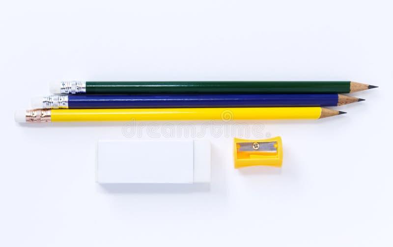 Точилка для карандашей, ластик, и много карандашей изолированных на белом пюре стоковое изображение
