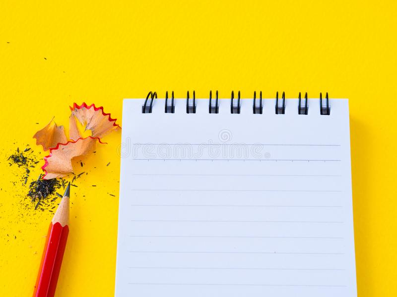 Точить красную точилку для карандашей и блокнот на желтой предпосылке стоковые изображения