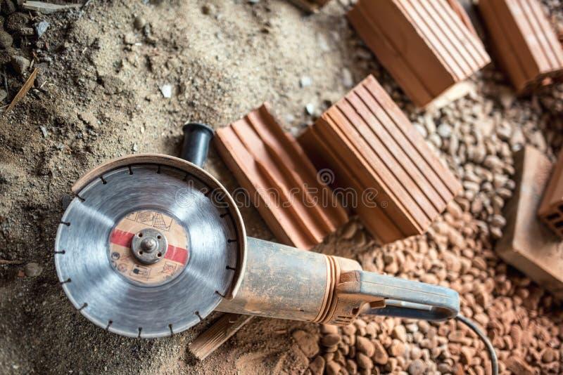 точильщик используемый на строительной площадке для резать кирпичи, твердые частицы Инструменты и кирпичи на новой строительной п стоковое изображение