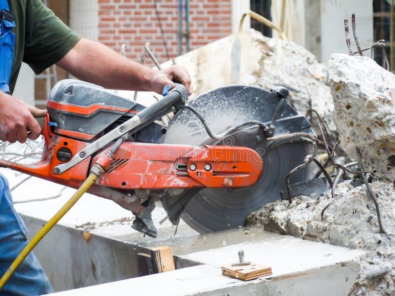 Точильщик удерживания оружий режа бетон стоковое изображение rf