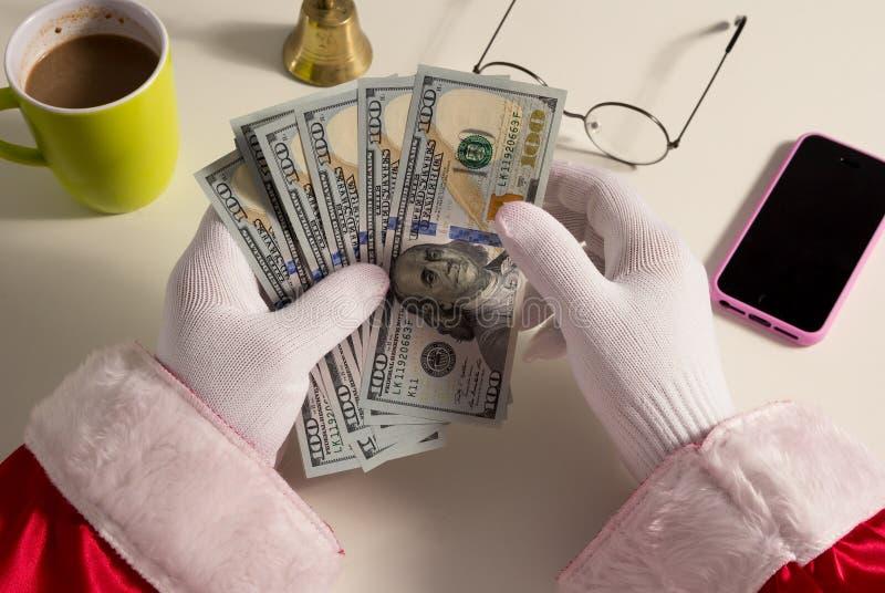 Точка зрения рук Санта Клауса держа деньги, доллары стоковая фотография