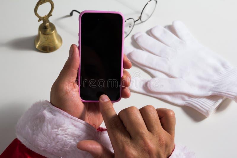 Точка зрения рук Санта Клауса касаясь экрану клетки p стоковые изображения rf