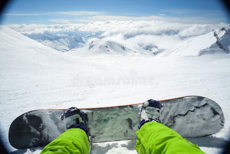 Точка зрения снятая мужского snowboarder лежа на снеге стоковые изображения